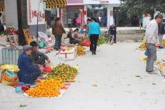 Men are selling mandarins at the fruits market, Xingping, China Stock Photo