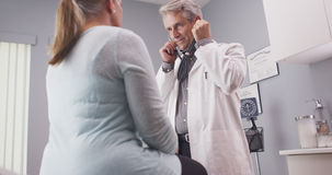 Male senior doctor listening to patient vitals with stethoscope Stock Images