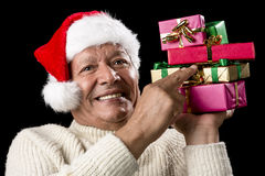 Male Senior Firmly Pointing At Six Wrapped Gifts. Smiling aged man emphatically pointing with two fingers at six Christmas presents wrapped in gold, green and Royalty Free Stock Images
