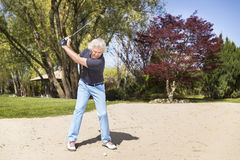Male senior golf player in bunker. Stock Photos
