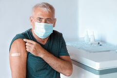 Free Male Senior In Face Mask After Receiving COVID-19 Vaccine. Elderly Man Feeling Good On Getting Coronavirus Vaccine Stock Images - 220929464