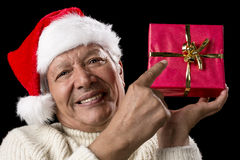 Male Senior Pointing At Red Wrapped Christmas Gift. Friendly old man with red Father Christmas cap in white pullover. He is pointing his right index finger at a Stock Photography