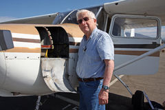 Male senior and private airplane. A senior citizen stands by a private aircraft, a Cessna 172 Royalty Free Stock Photography