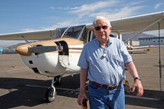 Male senior and private airplane. A senior citizen walks away from a private aircraft, a Cessna 172 Royalty Free Stock Photos