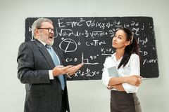 Male professor and young woman against chalkboard in classroom. Male senior professor and young female student against chalkboard in classroom. Human emotions Stock Images