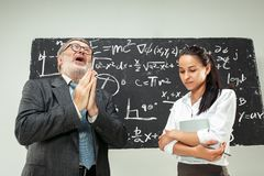 Male professor and young woman against chalkboard in classroom. Male senior professor and young female student against chalkboard in classroom. Human emotions Royalty Free Stock Images