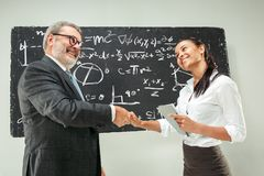 Male professor and young woman against chalkboard in classroom. Male senior professor and young female student against chalkboard in classroom. Human emotions Royalty Free Stock Photography