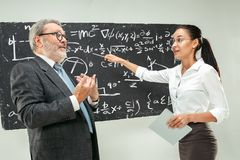 Male professor and young woman against chalkboard in classroom. Male senior professor and young female student against chalkboard in classroom. Human emotions Stock Photos