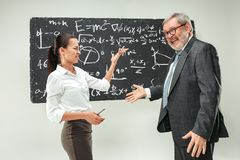 Male professor and young woman against chalkboard in classroom. Male senior professor and young female student against chalkboard in classroom. Human emotions Royalty Free Stock Photo