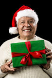 Male Senior With Santa Claus Cap and Green Gift. Shyly grinning old gentleman with a red Santa Claus cap and white knitted pullover. He is holding a green Royalty Free Stock Images