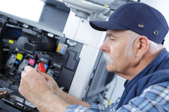 Male senior technician repairing printer at office Stock Images