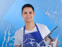 Male servant cleaning glass with squeegee. Portrait of young male servant cleaning glass with squeegee over blue background royalty free stock images