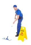 Male servant mopping floor by wet floor sign. Full length of male servant mopping floor by Wet Floor Sign over white background Royalty Free Stock Photography