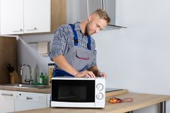 Male Serviceman Using Screwdriver To Repair Microwave. Happy Male Serviceman Using Screwdriver To Repair Microwave In Kitchen At Home royalty free stock photography