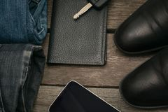 Male set for day from wallet, jeans and car key on wooden board. Flat lay. Top view Stock Photos