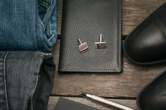 Male set for day from wallet, jeans and cufflinks on wooden board. Flat lay. Top view Royalty Free Stock Photos