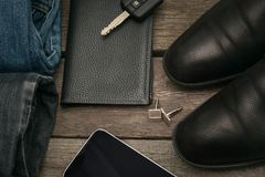 Male set for day from wallet, jeans, smartphone and car key on wooden board. Flat lay.  Royalty Free Stock Images