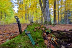 Male set - knives and watches. Black knife and smart watch in au. Tumn forrest Royalty Free Stock Photos