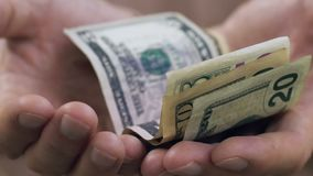 Male shaking hands holding few dollar banknotes, begging for money, close up. Stock footage stock video footage
