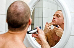Male shaving in bathroom. In front of the mirror Stock Image