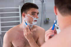 Male shaving his face and looking at the mirror. In the modern tiled bathroom at home Royalty Free Stock Images