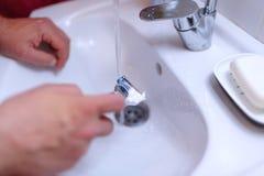 Male shaving razor blade hand, shaving beard in a bathroom. Male shaving razor blade hand close up, shaving beard in a bathroom Royalty Free Stock Image