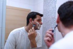 Male shaving with razor and shaving cream in bathroom. Young male shaving with razor and shaving cream in bathroom Stock Photos
