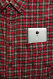 Male shirt with a cell phone in the pocket. Male checkered cowboy`s shirt with a cell phone in the pocket royalty free stock photography