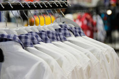 Male shirt on hangers in clothing store Stock Photos