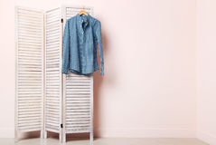 Male shirt. Hanging on folding screen on a beige background Royalty Free Stock Photos