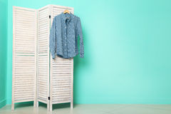 Male shirt. Hanging on folding screen on a green background Stock Images