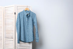 Male shirt. Hanging on folding screen on a grey background Royalty Free Stock Images