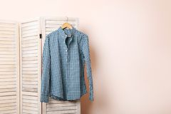 Male shirt. Hanging on folding screen on a beige background Stock Photo