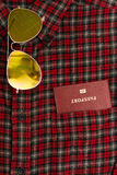 Male shirt with a passport in the pocket. Male checkered cowboy`s shirt with a passport in the pocket and sunglasses Stock Images