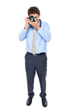 Male in shirt and tie takes photo with dslr camera. Young businessman in blue shirt and necktie takes photo with dslr camera, studio shoot isolated on white Stock Photography