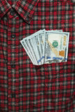 Male shirt with US dollars in the pocket. Male checkered cowboy`s shirt with unsafely stored money in the pocket royalty free stock image