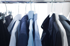 Male shirts hanging on a rack. Set of male elegant shirts hanging on a rack, businessman outfit and wardrobe Stock Photo