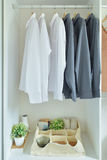 Male shirts hanging in wardrobe. Male shirts hanging in white wardrobe Royalty Free Stock Images