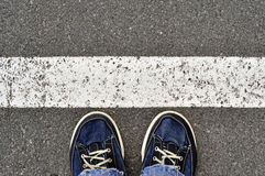 Male shoes on the asphalt road with white line, step into. ? Stock Image