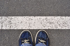 Male shoes on the asphalt road with white line, step into. Top View of Male shoes on the asphalt road with white line, Step into Stock Image