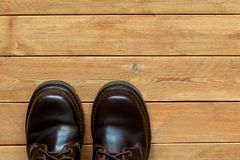 Male shoes on a wooden background. Male shoes on a brown wooden background Royalty Free Stock Image