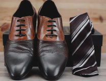 Male shoes and tie. In wooden background Stock Image