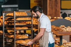 Male shop assistant in apron arranging fresh pastry. In supermarket Stock Images