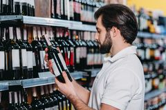 Male shop assistant arranging alcohol. In supermarket stock photography