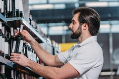 Male shop assistant arranging alcohol. In supermarket royalty free stock image