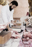 Male shop assistant carving meat. Glad young male seller cutting meat to sell in butcher's shop Stock Photography