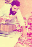 Male shop assistant carving meat. Positive young male seller cutting meat to sell in butcher's shop Royalty Free Stock Photo