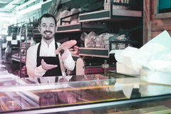 Male shop assistant demonstrating delicious loaves of bread in b. Happy english male shop assistant demonstrating delicious loaves of bread in bakery royalty free stock image