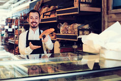 Male shop assistant demonstrating delicious loaves of bread in b. Happy english male shop assistant demonstrating delicious loaves of bread in bakery stock photo