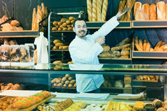 Male shop assistant demonstrating delicious loaves of bread in b. Happy spanish male shop assistant demonstrating delicious loaves of bread in bakery stock photo